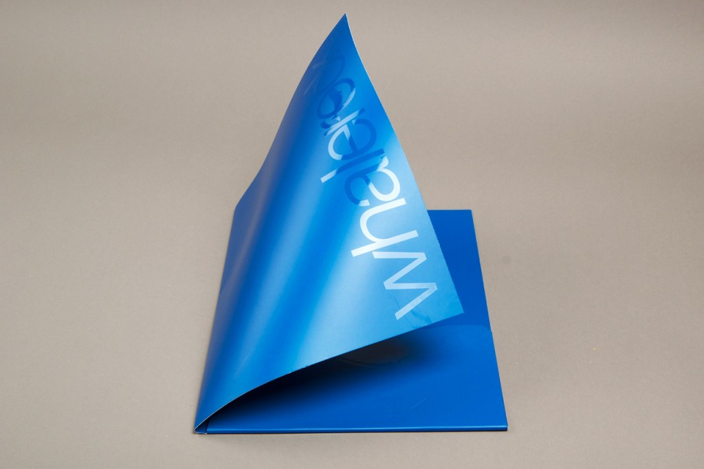 Cover of a folder is bent with a tape to highlight spot UV varnish